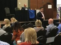 Dr. Edward Espinosa [and Terry Bauer; CEO of Specialdocs behind at Table] speak to a crowd of Physicians at the 2017 CMT FORUM in Atlanta, Saturday, Oct. 28, 2017.